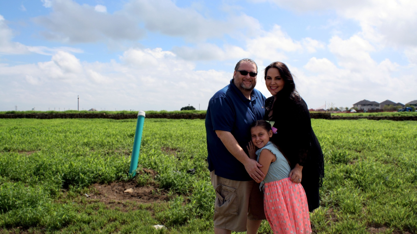 Scott, Marie and Alexandra Bailey standing on the plot where their house is being built in Prosper at the Windsong Ranch planned community (before construction began).